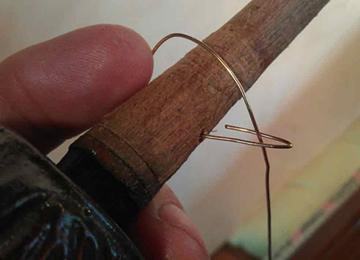 feed the string through the smallest hole and bend back the half centimeter on itself